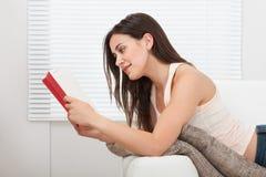 妇女阅读书,当说谎在沙发时 库存照片