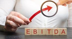妇女阻止在木块的箭头与词Ebitda 在兴趣、税、减价偿还费前的收入 ?? 免版税库存照片
