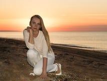 妇女降低了在沙子的手在海滨 免版税库存照片