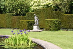 妇女雕象和一个池塘赤柏松修剪的花园的在Tiverton,德文郡,英国从事园艺 免版税库存照片