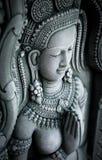 妇女雕象在墙壁上的在古庙在泰国 免版税库存照片