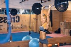 妇女震动她的在健身房的肩膀 免版税图库摄影