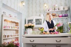 妇女非常热忱对她工作在花店 图库摄影