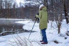 妇女非职业摄影师采取在湖的一个冬天风景森林拷贝空间的 库存照片
