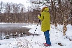 妇女非职业摄影师采取在湖的一个冬天风景森林拷贝空间的 库存图片