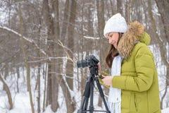 妇女非职业摄影师采取在湖的一个冬天风景森林拷贝空间的 免版税库存图片