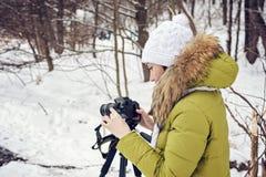 妇女非职业摄影师采取在湖的一个冬天风景森林拷贝空间的 免版税图库摄影