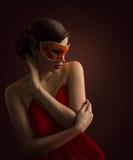 妇女面具,摆在红色狂欢节化妆舞会的性感的时装模特儿 库存照片