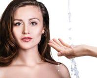 妇女面孔和倾吐的水在手中 库存图片