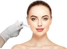 妇女面孔和手在手套与做射入的注射器 库存图片