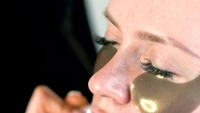 妇女面孔特写镜头与下面眼睛补丁的 应用在面孔的化妆师化妆音调的基础使用刷子 股票录像