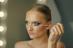妇女面孔秀丽 妇女用途染睫毛油涂药器刷子,构成 妇女申请在睫毛的染睫毛油构成,看 beauvoir 免版税库存图片