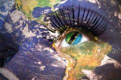 妇女面对与行星地球纹理和坦桑尼亚旗子在眼睛里面 免版税库存照片