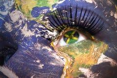 妇女面对与行星地球纹理和牙买加旗子在眼睛里面 免版税图库摄影