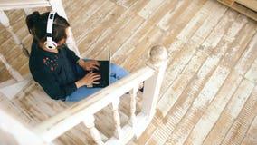 妇女顶视图有放松与膝上型计算机的耳机的,当在家时坐台阶在客厅 库存照片