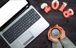 妇女顶视图递拿着杯子热的咖啡、开放膝上型计算机有空白的白色屏幕的和新年2018标志标志 免版税库存图片
