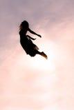 妇女飞行剪影通过天空 库存图片