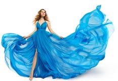 妇女飞行蓝色礼服,在长的挥动的褂子,在白色的振翼的织品的时装模特儿跳舞 免版税库存图片