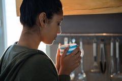妇女食用咖啡在厨房 图库摄影