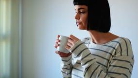 妇女食用咖啡在客厅4k 股票录像