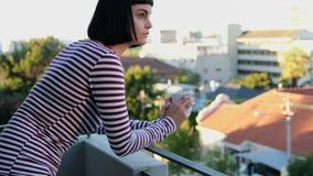 妇女食用咖啡在阳台4k 股票录像