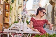 妇女食用意大利咖啡在街道上的咖啡馆在托斯卡纳 免版税库存照片
