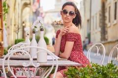 妇女食用意大利咖啡在街道上的咖啡馆在托斯卡纳 免版税库存图片