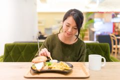 妇女食用炸薯条在餐馆 库存图片