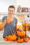 妇女食用热的饮料在万圣夜装饰了厨房 免版税库存照片