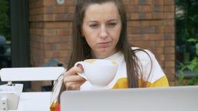 妇女饮料咖啡和使用膝上型计算机 影视素材