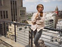 妇女饮用的咖啡和享受从阳台的城市视图 库存图片