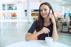 妇女饮用的咖啡和叫与手机 免版税库存图片
