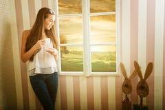 妇女饮用的咖啡在一个美好的早晨在窗口里 免版税库存图片