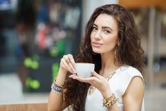 妇女饮用的咖啡在咖啡馆超级市场 库存照片