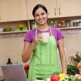 妇女饮用的咖啡在她的厨房里 免版税库存图片