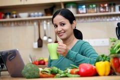妇女饮用的咖啡在她的厨房里 库存图片