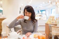 妇女饮用的咖啡在蛋糕商店 免版税库存照片