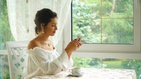 妇女饮用的咖啡在餐馆和写一则消息 股票录像
