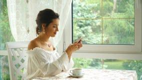 妇女饮用的咖啡在餐馆和写一则消息 影视素材