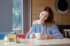 妇女饮用的咖啡在餐馆的早晨 库存图片