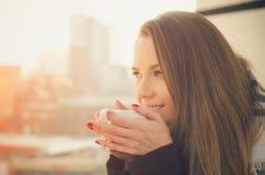 妇女饮用的咖啡或茶与杯子在阳台 免版税库存图片