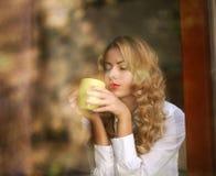 妇女饮用的咖啡户内,享受饮料芳香  免版税库存图片