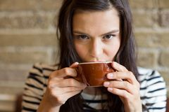 妇女饮用的咖啡特写镜头在咖啡馆的 免版税库存图片