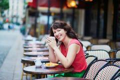 妇女饮用的咖啡用在巴黎人咖啡馆的新月形面包 库存图片