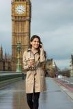 妇女饮用的咖啡谈话在手机,大本钟,伦敦 库存照片