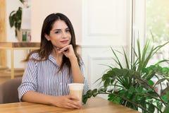 妇女饮用的咖啡,放松在坐在窗口附近的咖啡馆 免版税库存照片