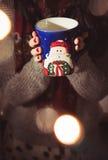 妇女饮用的咖啡/茶/热巧克力在圣诞节季节期间 库存图片