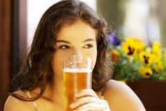 妇女饮用的啤酒的画象在酒吧的 库存图片