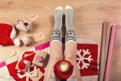 妇女饮用的热奶咖啡咖啡和坐木地板 女性腿特写镜头在温暖的袜子的与与圣诞节的一头鹿 免版税库存图片