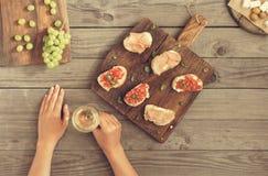 妇女饮用的酒和吃酒的开胃菜 免版税库存图片